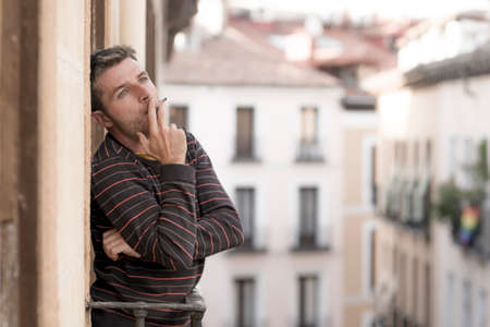 urban lifestyle emotional portrait of young handsome man sad and depressed smoking cigarette thoughtful at home balcony leaning unhappy feeling bittered suffering some problem Imagens
