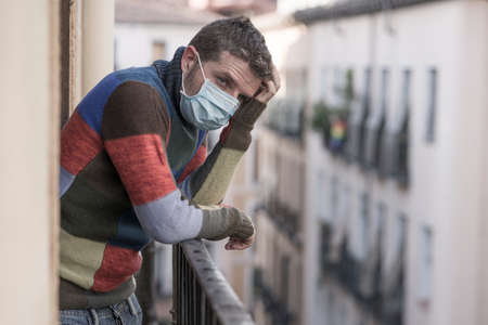 stay home quarantine portrait of of 30s handsome man in face mask sad and depressed at home balcony during covid19 lockdown feeling worried and scared looking to city street