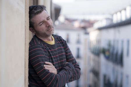 urban lifestyle emotional portrait of young attractive and depressed man at home balcony leaning upset feeling desperate suffering depression problem looking at city street thoughtful