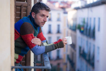 urban lifestyle emotional portrait of young attractive man sad and depressed at home balcony drinking coffee cup suffering depression problem looking thoughtful at city street