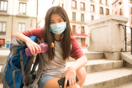 new normal holidays travel in Europe - young beautiful and happy Asian Chinese tourist woman with face mask and backpack enjoying city tour excited and free after covid19 lockdown