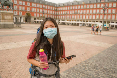 new normal holidays travel in Europe - young happy and beautiful Asian Chinese tourist woman in mask wearing backpack and mobile phone enjoying city tour smiling cheerful