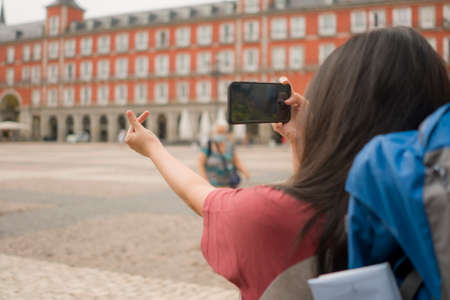 new normal holidays travel in Europe - young beautiful and happy Asian Korean tourist woman with face mask and backpack taking pictures with mobile phone enjoying city tour excited