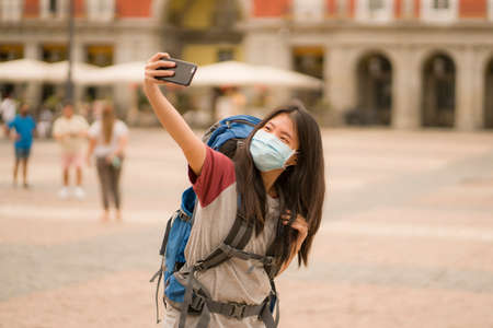 new normal holidays travel in Europe - young happy and beautiful Asian Korean tourist woman wearing mask taking selfie with mobile phone enjoying city sightseeing and urban tourism