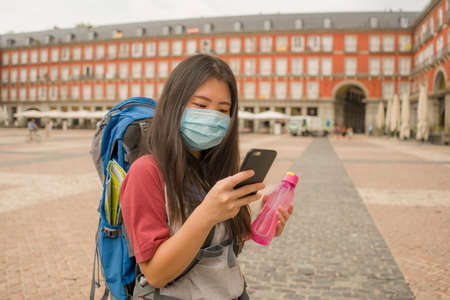 new normal holidays travel in Europe - young happy and beautiful Asian Japanese tourist woman in mask wearing backpack using mobile phone enjoying city tour and urban tourism
