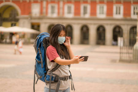 new normal holidays travel in Europe - young happy and beautiful Asian Chinese tourist woman in mask wearing backpack using mobile phone enjoying city tour and urban tourism Stock fotó