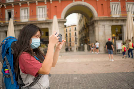 new normal holidays travel in Europe - young beautiful and happy Asian Chinese tourist woman with face mask and backpack taking pictures with mobile phone enjoying city tour excited