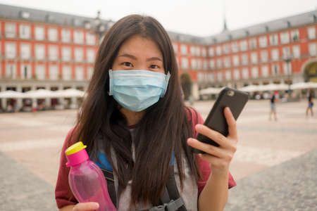 new normal holidays travel in Europe - young happy and beautiful Asian Korean tourist woman in mask wearing backpack and mobile phone enjoying city tour smiling cheerful