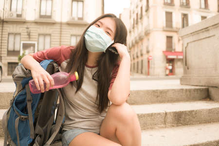 new normal holidays travel in Europe - young beautiful and happy Asian Korean tourist woman with face mask and backpack enjoying city tour excited and free after covid19 lockdown