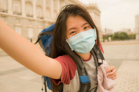 new normal holidays travel in Europe - young happy and beautiful Asian Japanese tourist woman wearing mask taking selfie with mobile phone enjoying city sightseeing and urban tourism Stock fotó