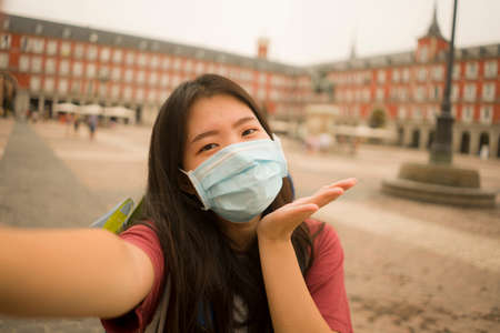 new normal holidays travel in Europe - young happy and beautiful Asian Chinese tourist woman wearing mask taking selfie with mobile phone enjoying city sightseeing and urban tourism