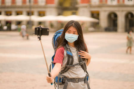 new normal holidays travel in Europe - young happy and beautiful Asian Chinese tourist woman in face mask taking selfie with mobile phone and stick enjoying city and urban sightseeing