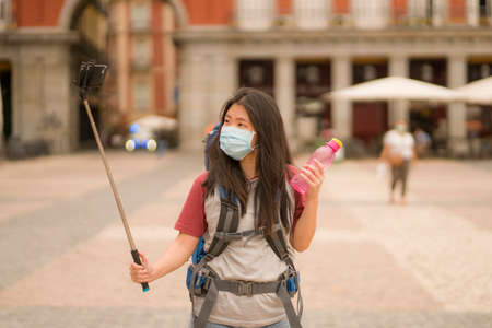 new normal holidays travel in Europe - young happy and beautiful Asian Japanese tourist woman in face mask taking selfie with mobile phone and stick enjoying city and urban sightseeing Stock fotó