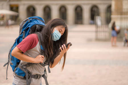 new normal holidays travel in Europe - young happy and beautiful Asian Korean tourist woman in mask wearing backpack using mobile phone enjoying city tour and urban tourism Stock fotó