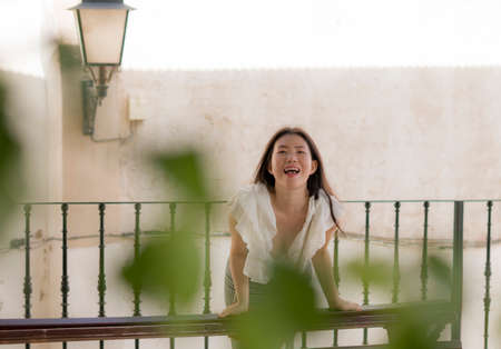 lifestyle portrait of young attractive and beautiful Asian Chinese woman outdoors at urban balcony in Spain enjoying summer holidays travel happy and carefree 版權商用圖片 - 153995658