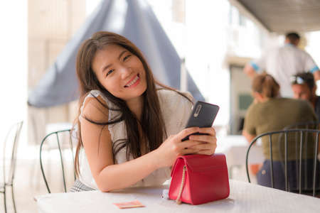 lifestyle portrait of young beautiful and sweet Asian Korean woman sitting happy outdoors at street cafe using internet travel and social media app in mobile phone relaxed 版權商用圖片 - 153995668