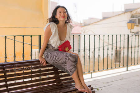 lifestyle portrait of young attractive and beautiful Asian Korean woman sitting outdoors at city park bench happy and relaxed touring Seville town in Spain during holidays travel in Europe Standard-Bild