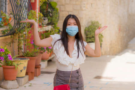 new normal tourism and travel - young happy and beautiful Asian Japanese woman in face mask visiting Seville in Spain enjoying Europe Summer holiday relaxed during city tour