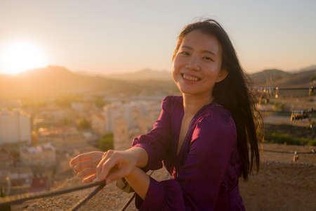 young happy and beautiful Asian Korean woman outdoors at viewpoint balcony enjoying sunset view of Spain town during Europe holiday travel feeling free and relaxed 版權商用圖片 - 154496133