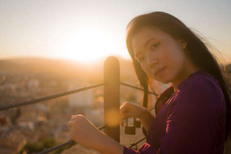 young happy and beautiful Asian Korean woman outdoors at viewpoint balcony enjoying sunset view of Spain town during Europe holiday travel feeling free and relaxed 版權商用圖片 - 154496328