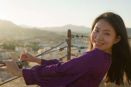 young happy and beautiful Asian Korean woman outdoors at viewpoint balcony enjoying sunset view of Spain town during Europe holiday travel feeling free and relaxed 版權商用圖片 - 154496344