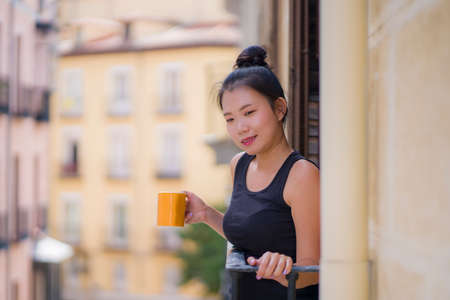 young beautiful and happy Asian Korean woman enjoying city view from hotel room balcony in Spain during holidays trip in Europe drinking coffee relaxed in urban background