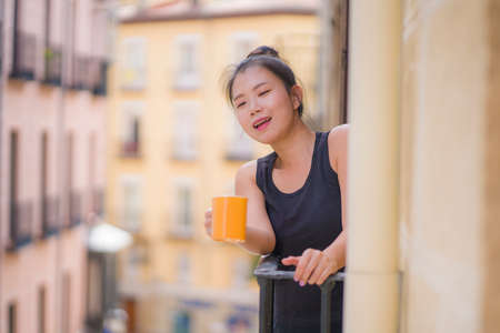 young beautiful and happy Asian Japanese woman enjoying city view from hotel room balcony in Spain during holidays trip in Europe drinking coffee relaxed in urban background