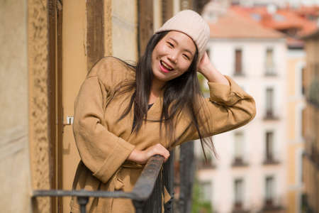 young happy and beautiful Asian Japanese woman in winter hat enjoying city view from hotel room balcony in Spain during holidays trip in Europe smiling cheerful in urban background