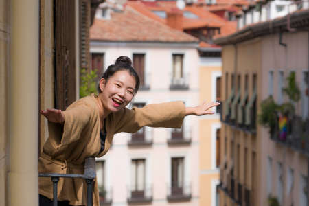 young happy and beautiful Asian Chinese woman in hair bun enjoying city view from hotel room balcony in Spain during holidays trip in Europe smiling cheerful in urban background