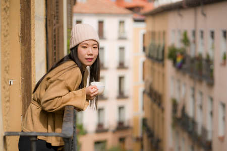 young beautiful and happy Asian Korean woman in winter hat enjoying city view from hotel room balcony in Spain during holidays trip in Europe drinking coffee relaxed in urban background