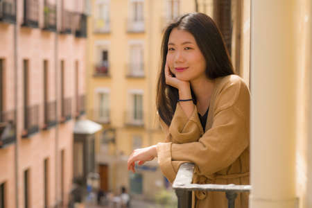 young happy and beautiful Asian Japanese woman enjoying city view from hotel room balcony in Spain during holidays trip in Europe smiling cheerful in urban background