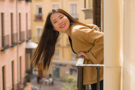 young happy and beautiful Asian Chinese woman enjoying city view from hotel room balcony in Spain during holidays trip in Europe smiling cheerful in urban background Фото со стока