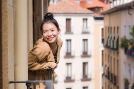 young happy and beautiful Asian Korean woman in hair bun enjoying city view from hotel room balcony in Spain during holidays trip in Europe smiling cheerful in urban background Фото со стока