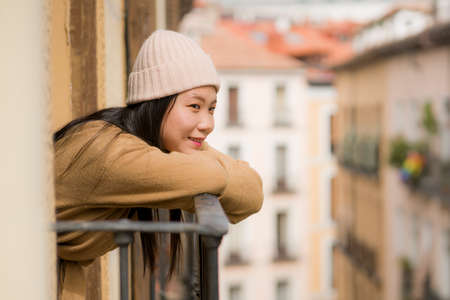 young happy and beautiful Asian Korean woman in winter hat enjoying city view from hotel room balcony in Spain during holidays trip in Europe smiling cheerful in urban background