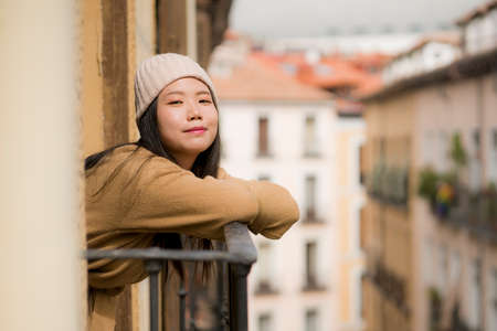 young happy and beautiful Asian Chinese woman in winter hat enjoying city view from hotel room balcony in Spain during holidays trip in Europe smiling cheerful in urban background Фото со стока