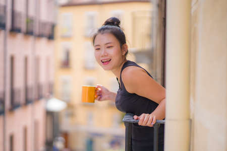 young beautiful and happy Asian Chinese woman enjoying city view from hotel room balcony in Spain during holidays trip in Europe drinking coffee relaxed in urban background