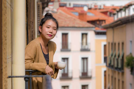 young happy and beautiful Asian Japanese woman enjoying city view from hotel room balcony in Spain during holidays trip in Europe drinking coffee smiling cheerful in urban background Фото со стока