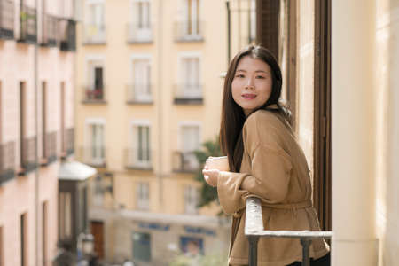 young happy and beautiful Asian Korean woman enjoying city view from hotel room balcony in Spain during holidays trip in Europe drinking coffee smiling cheerful in urban background