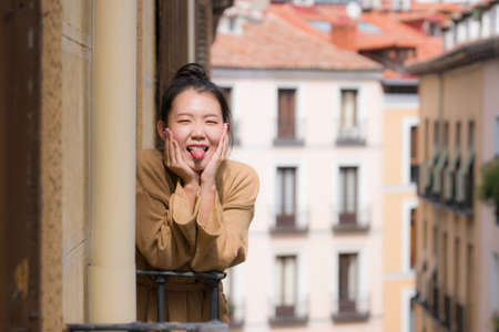 young happy and beautiful Asian Japanese woman in hair bun enjoying city view from hotel room balcony in Spain during holidays trip in Europe smiling cheerful in urban background