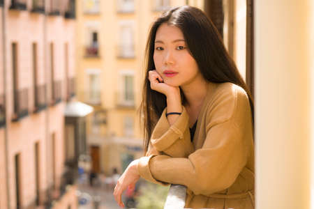 young happy and beautiful Asian Korean woman enjoying city view from hotel room balcony in Spain during holidays trip in Europe smiling cheerful in urban background Фото со стока