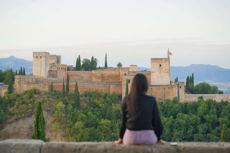 back portrait of young beautiful and relaxed woman having Summer holidays in Spain enjoying cheerful beautiful view at Alhambra of Granada in tourism travel and lifestyle concept 版權商用圖片