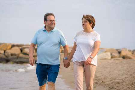 happy retired mature couple walking on the beach - pensioner woman and her husband taking romantic walk together enjoying sweet holidays in lifetime relationship and love concept