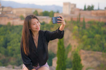 lifestyle portrait of young beautiful and happy Asian Korean tourist woman having Summer holidays in Europe taking selfie with mobile phone at beautiful Alhambra of Granada in Spain 版權商用圖片