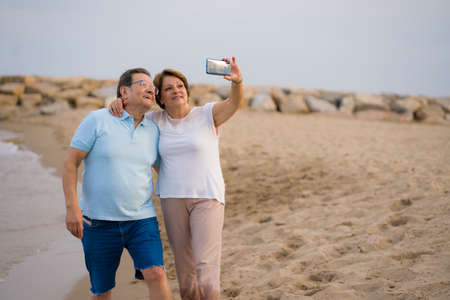 happy pensioner woman and her husband taking romantic walk taking selfie - happy retired mature couple walking on the beach during holidays taking self portrait with mobile phone