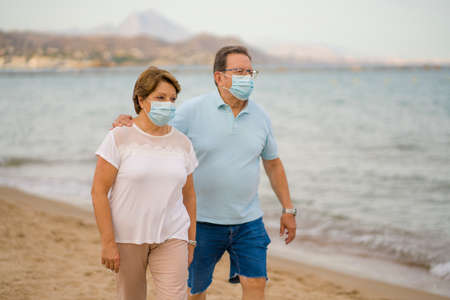 pensioner woman and her husband taking romantic walk together - happy retired mature couple in face mask walking on the beach in new normal holidays trip during covid19 版權商用圖片