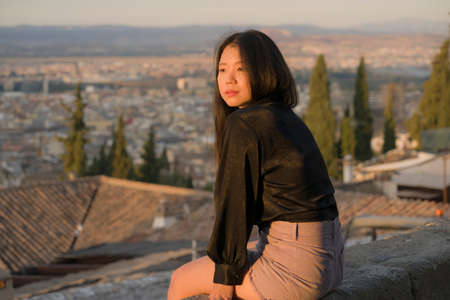 lifestyle portrait of young beautiful and happy Asian Korean tourist woman having Summer holidays in Europe enjoying cheerful visiting beautiful Alhambra of Granada in Spain