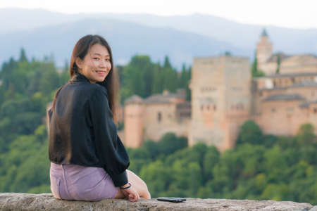 lifestyle portrait of young beautiful and happy Asian Japanese tourist woman during Summer holidays in Europe sitting cheerful enjoying beautiful view of Alhambra in Granada Spain