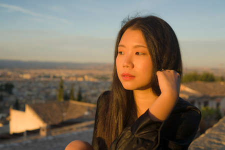 lifestyle portrait of young beautiful and happy Asian Chinese tourist woman enjoying Summer holidays in Europe walking cheerful visiting beautiful Alhambra in Granada Spain