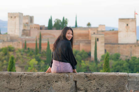 lifestyle portrait of young beautiful and happy Asian Chinese tourist woman during Summer holidays in Europe sitting cheerful enjoying beautiful view of Alhambra in Granada Spain