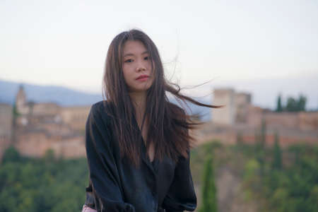 lifestyle portrait of young beautiful and happy Asian Korean tourist woman during Summer holidays in Europe sitting cheerful enjoying beautiful view of Alhambra in Granada Spain Stock Photo